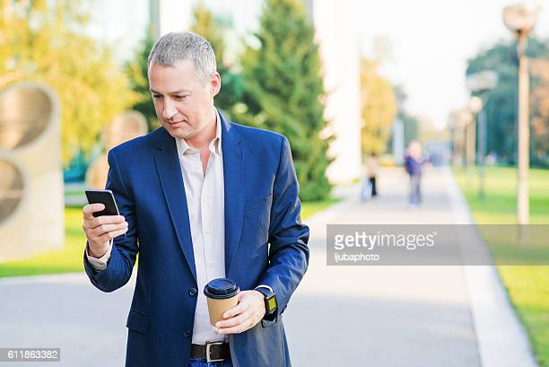 Texting businessman having coffee break holding coffee