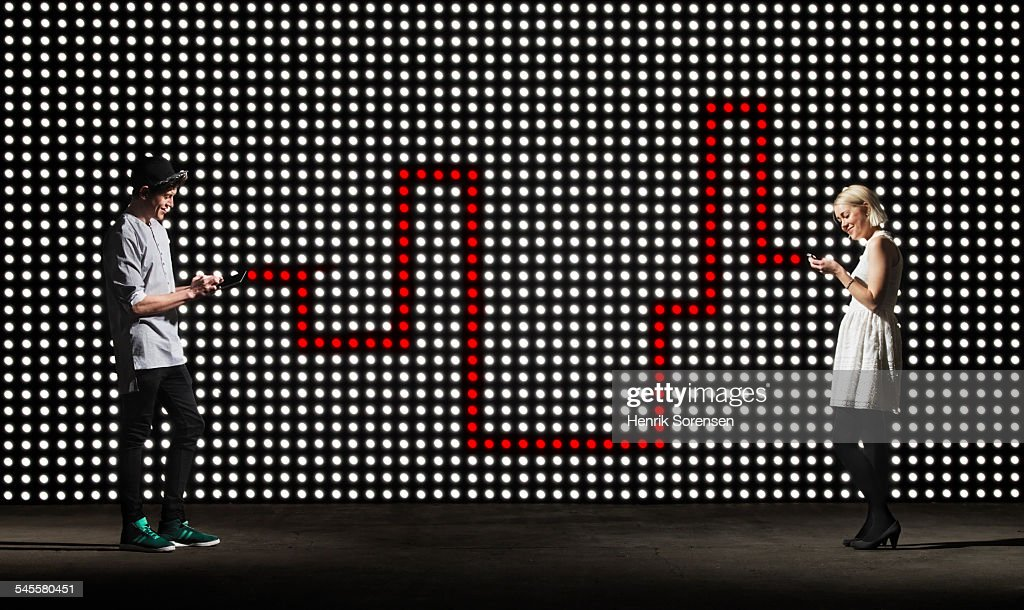texting in front of lightwall : Stock Photo