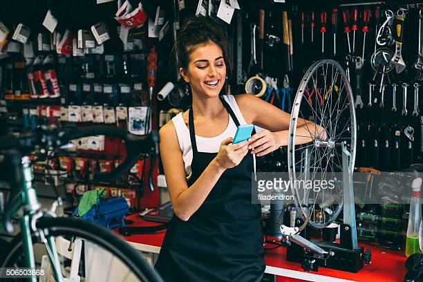 Texting on the phone while fixing a bicycle