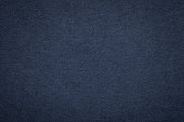 Texture of old navy blue paper background, closeup. Structure of dense dark denim kraft cardboard.