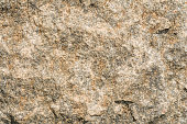 Texture of the surface of an antique stone wall under natural light by sunlight, abstract background
