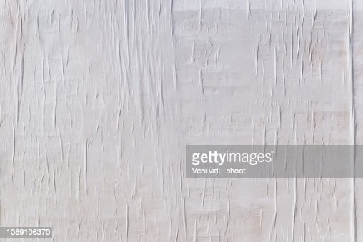 Texture of wet white folded paper on an outdoor poster wall, crumpled paper background : Stock Photo