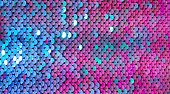 Abstract colorful Texture scales with bright Sequins close-up. Glamor Background with shiny blue, purple and Magenta sequins on fabric, macro. Beautiful Holiday Wallpaper with pattern of round Sequins