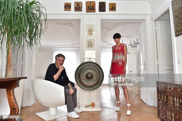 TFrench fashion designer Olivier Lapidus poses during a photo session with a model wearing one of his hautecouture creations at his workshop in Paris...
