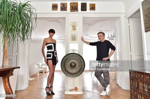 TFrench fashion designer Olivier Lapidus poses with a model wearing one of his readytowear creations at his workshop in Paris on June 28 2017 / AFP...