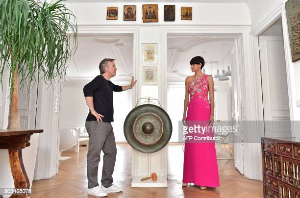 TFrench fashion designer Olivier Lapidus poses with a model wearing one of his hautecouture creations at his workshop in Paris on June 28 2017 / AFP...