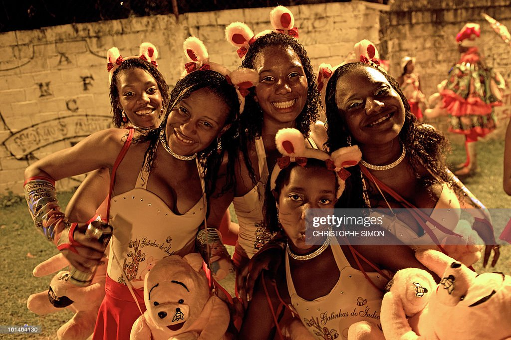 T'Gatinhas' (Pussycats) of the local 'Indio' carnival group of the Guadalupe neighborhood in northern Rio de Janeiro, Brazil, take part in their 'Bate Bola' traditional parade on February 10, 2013. AFP PHOTO/Christophe Simon