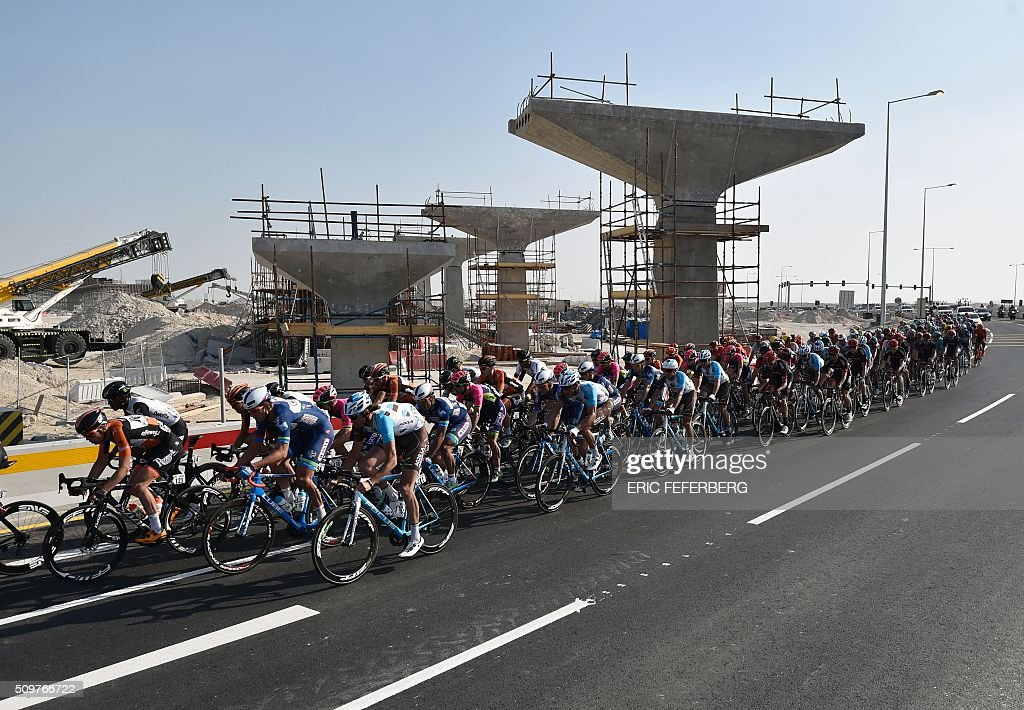Tha pack rides in front of construction during the 5th and final stage of the 15th Tour of Qatar, between Sealine Beach Resort and Doha Corniche, on February 12, 2016, in Qatar. Mark Cavendish won the overall gold jersey, Alexander Kristoff finished second and Greg Van Avermaet finished third in the overall classification of the tour. / AFP / ERIC FEFERBERG