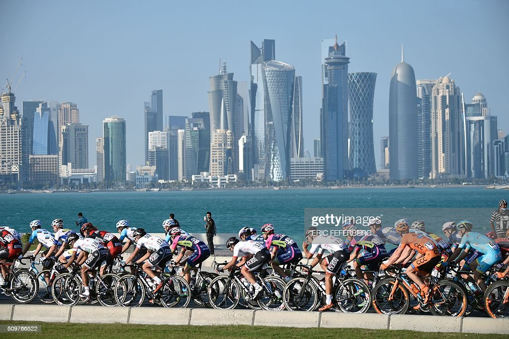 Tha pack rides in front of Doha skyline during the 5th and final stage of the 15th Tour of Qatar, between Sealine Beach Resort and Doha Corniche, on February 12, 2016, in Qatar. Mark Cavendish won the overall gold jersey, Alexander Kristoff finished second and Greg Van Avermaet finished third in the overall classification of the tour. / AFP / ERIC FEFERBERG
