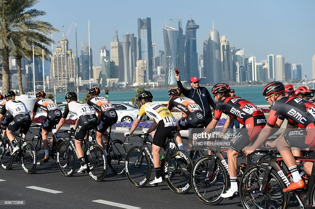 Tha pack, with Britain's Mark Cavendish (C, golden jersey) of Dimension Data team, rides in front of Doha skyline during the 5th and final stage of the 15th Tour of Qatar, between Sealine Beach Resort and Doha Corniche, on February 12, 2016, in Qatar. / AFP / ERIC FEFERBERG