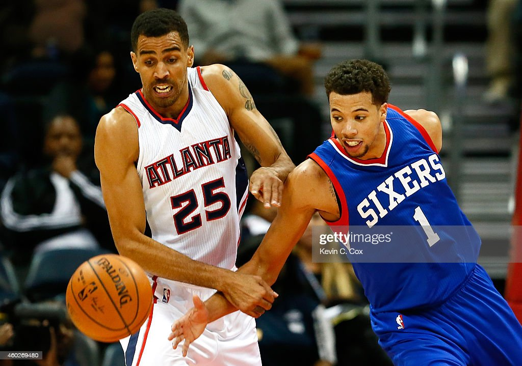 Thabo Sefolosha #25 of the Atlanta Hawks and Michael Carter-Williams #1 of the Philadelphia 76ers battle for a loose ball at Philips Arena on December 10, 2014 in Atlanta, Georgia.