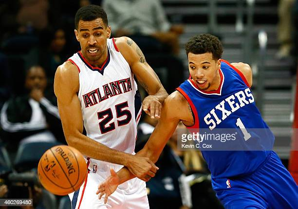 Thabo Sefolosha of the Atlanta Hawks and Michael CarterWilliams of the Philadelphia 76ers battle for a loose ball at Philips Arena on December 10...