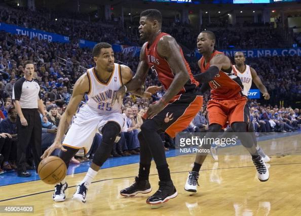 Thabo Sefolosha of the Oklahoma City Thunder handles the ball against Amir Johnson of the Toronto Raptors at the Chesapeake Arena on December 2013 in...