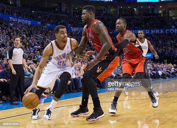 Thabo Sefolosha of the Oklahoma City Thunder handles the ball against Amir Johnson of the Toronto Raptors at the Chesapeake Arena on December 2013 in...