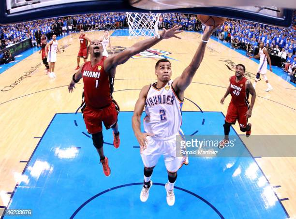 Thabo Sefolosha of the Oklahoma City Thunder lays the ball up in front of Chris Bosh of the Miami Heat in the second half in Game One of the 2012 NBA...