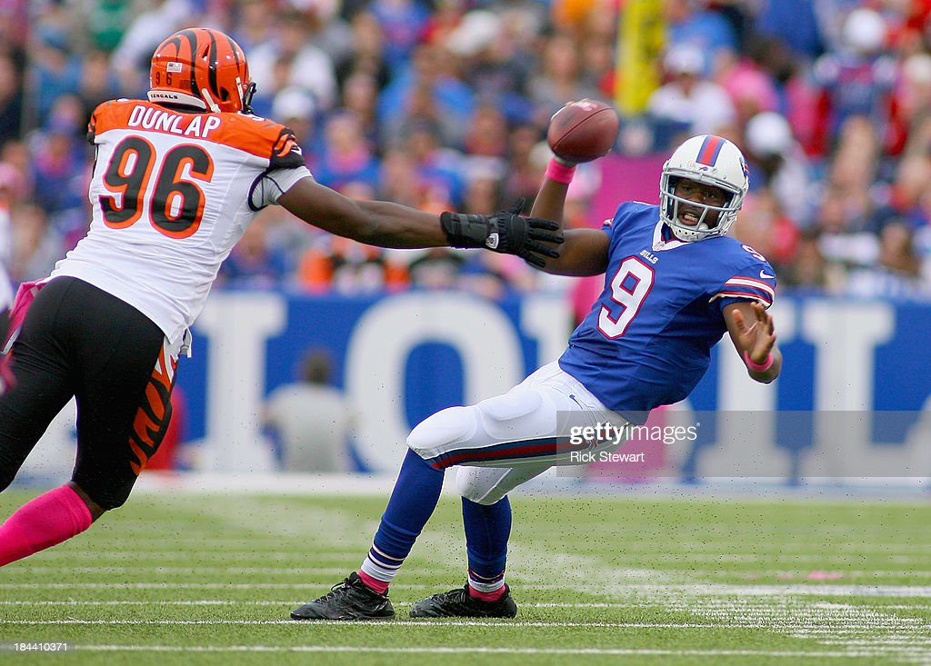 Thad Lewis #9 of the Buffalo Bills avoids a sack by <a gi-track='captionPersonalityLinkClicked' href=/galleries/search?phrase=Carlos+Dunlap&family=editorial&specificpeople=4489431 ng-click='$event.stopPropagation()'>Carlos Dunlap</a> #96 of the Cincinnati Bengals at Ralph Wilson Stadium on October 13, 2013 in Orchard Park, New York.