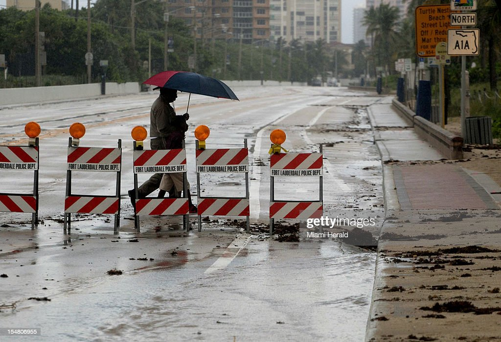 Thaddeus Hamilton, of the Broward County Soil and Water Conservation District, and his grandson Christian, 6, walk across a closed A1A at Sunrise Blvd. High tides and wind driven waves closed the road on Ft. Lauderdale Beach, Florida, Friday, October 26, 2012.