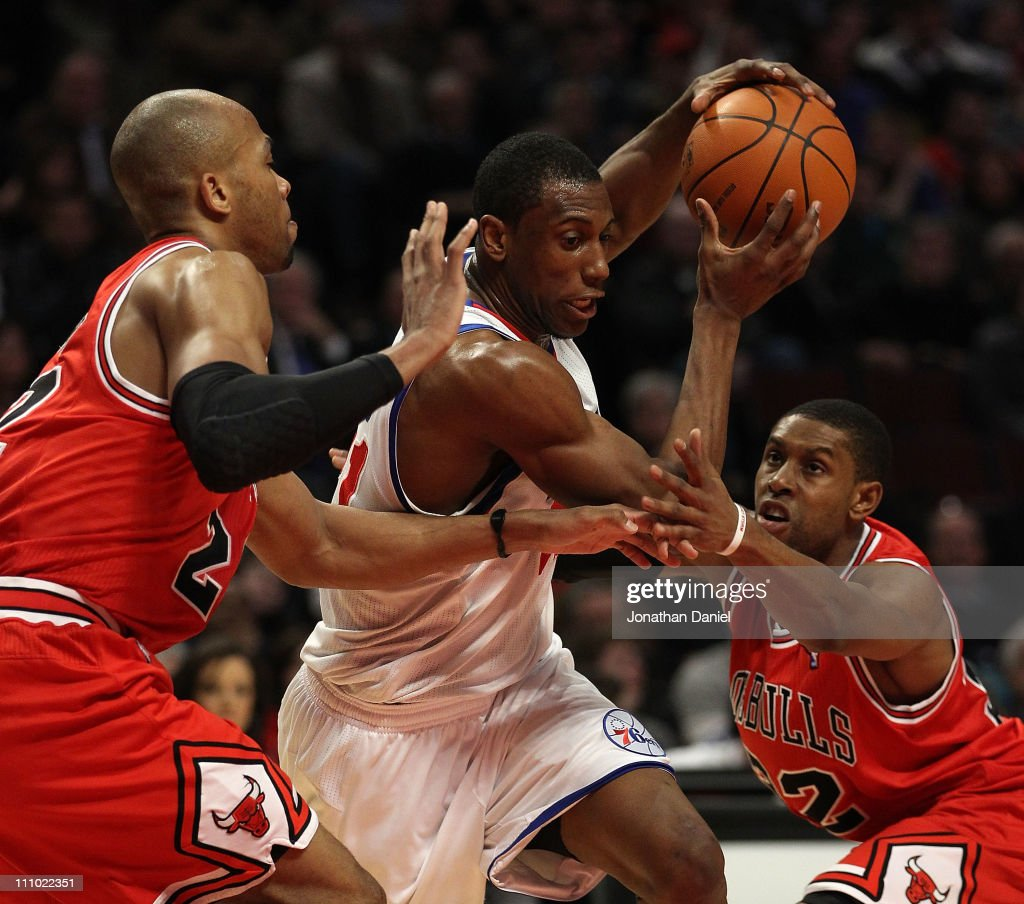 Thaddeus Young of the Philadelphia 76ers drives between Taj Gibson and CJ Watson of the Chicago Bulls at the United Center on March 28 2011 in...