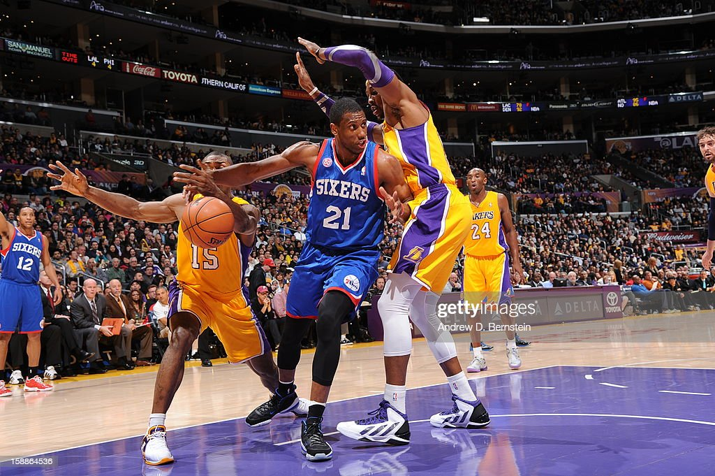 Thaddeus Young #21 of the Philadelphia 76ers goes to the basket against Metta World Peace #15 and Dwight Howard #12 of the Los Angeles Lakers at Staples Center on January 1, 2013 in Los Angeles, California.