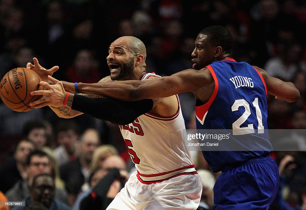 Thaddeus Young #21 of the Phildelphia 76ers tries to knock the ball away from Carlos Boozer #5 of the Chicago Bulls at the United Center on February 28, 2013 in Chicago, Illinois.