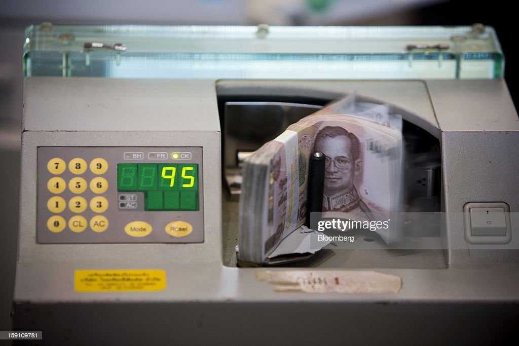 Thai 1000 Baht banknotes are counted by a currency counting machine at the Bangkok Bank Pcl. headquarters in Bangkok, Thailand, on Tuesday, Jan. 8, 2013. Thailand's economy may have expanded 5.7 percent in 2012 and will grow 5 percent in 2013, the finance ministry said on Dec. 26. Photographer: Brent Lewin/Bloomberg via Getty Images