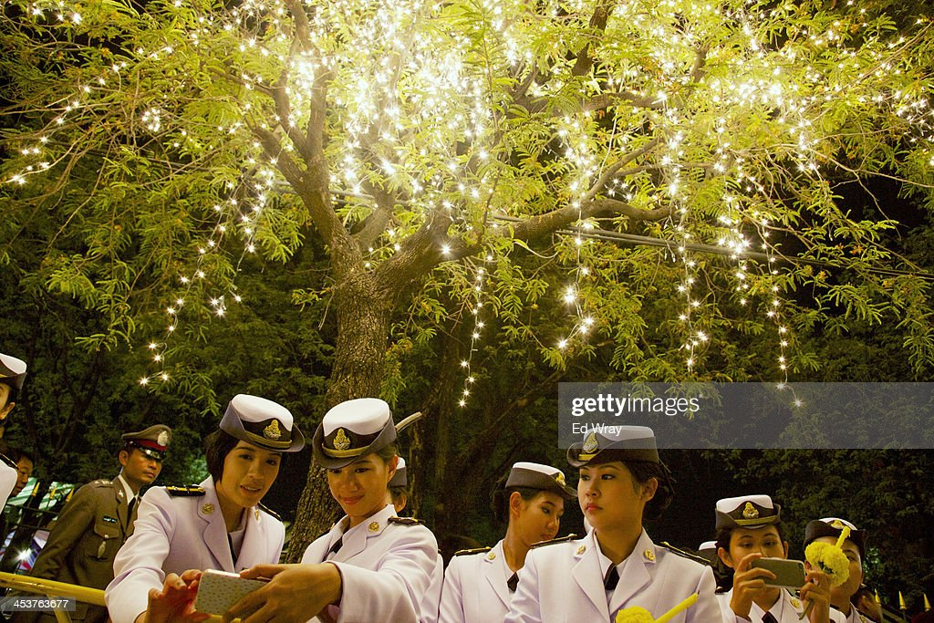 Thai Airforce cadets look at mobile phone images under a tree decorated for the Thai King Bhumibol Adulyadej's 86th birthday after a celebration on December 5, 2013 in Bangkok, Thailand. The tension between police and anti-government protesters has calmed as the protesters have temporarily agreed to halt their activities to pay respect to the King on his birthday.