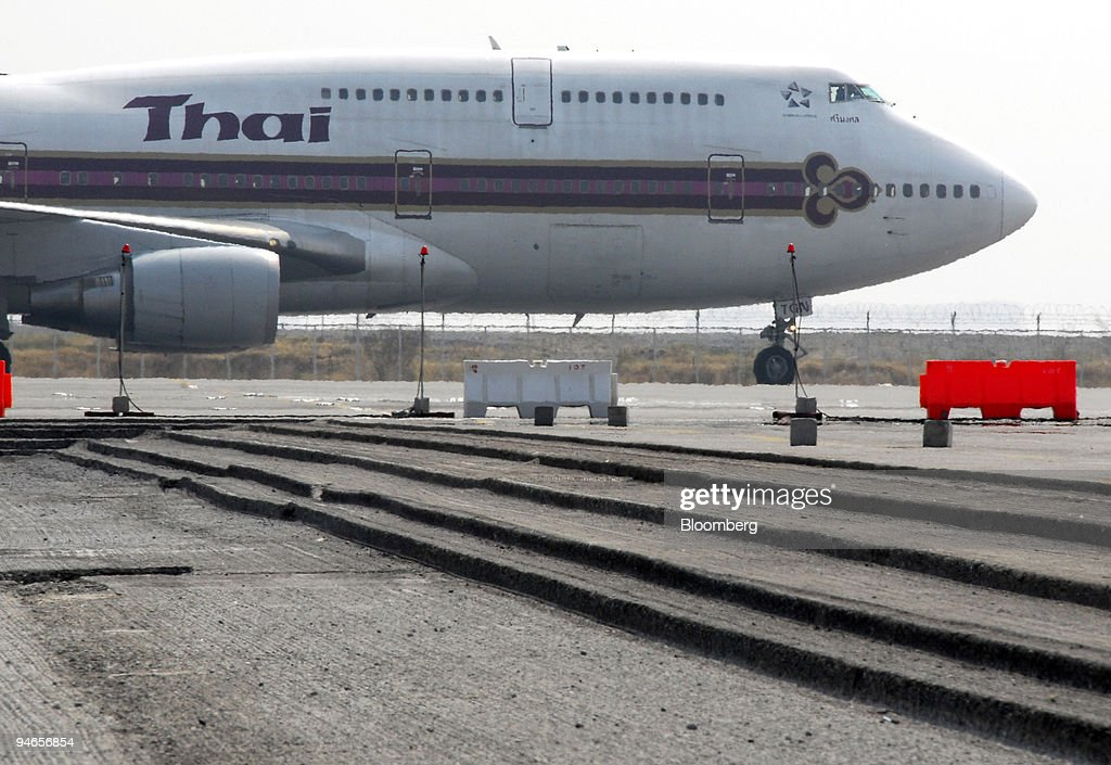 Thai Airways jet airplane approaches an area where several layers of asphalt has been excavated on the apron of Bangkok's new Suvarnabhumi Airport...