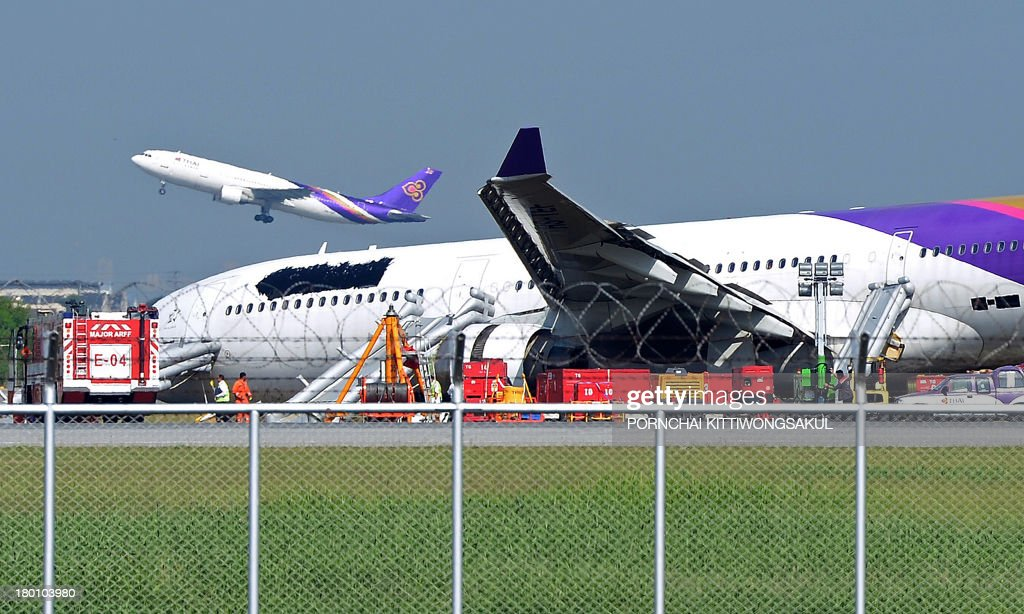 A Thai Airways plane (L) takes off as another (R), with its logo and name covered up, rests on ground the morning after it skidded off the runway at Suvarnabhumi International Airport in Bangkok on September 9, 2013. The incident late on September 8, which injured more than a dozen passengers, involved an Airbus 330-300 carrying 287 passengers and 14 crew members on a flight from Guangzhou, the carrier said.