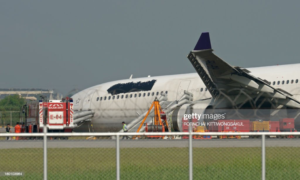 A Thai Airways plane, with its logo and name covered up, rests on ground the morning after it skidded off the runway at Suvarnabhumi International Airport in Bangkok on September 9, 2013. The incident late on September 8, which injured more than a dozen passengers, involved an Airbus 330-300 carrying 287 passengers and 14 crew members on a flight from Guangzhou, the carrier said. AFP PHOTO / PORNCHAI KITTIWONGSAKUL