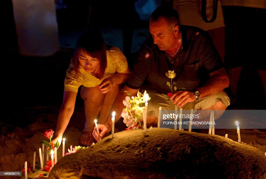 Thai and foreign tourists place candles on a sand sculpture during commemorations on the the tenth anniversary of the 2004 tsunami at Patong beach in...