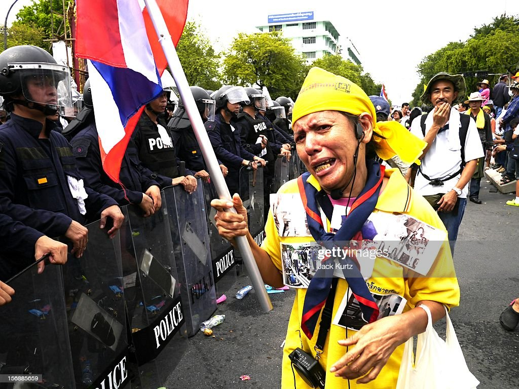 A Thai anti government protester confrontd riot police duringg an anti government protest on November 24, 2012 in Bangkok, Thailand. The Pitak Siam group is rallying to demand the resignation of the government.