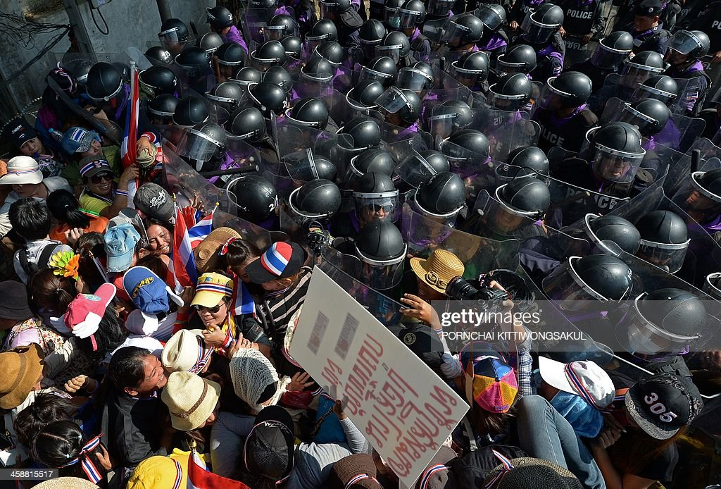 Thai anti government protesters battle with riot policemen during a rally outside the house of Prime Minister Yingluck Shinawatra in Bangkok on December 22, 2013. Tens of thousands of Thai anti-government protesters massed ahead of a major rally aimed at toppling the premier, paralysing parts of central Bangkok a day after the main opposition party declared a boycott of snap polls. AFP PHOTO / PORNCHAI KITTIWONGSAKUL
