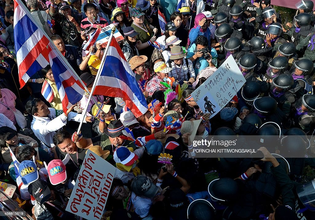 Thai anti government protesters battle with riot policemen during a rally outside the house of Prime Minister Yingluck Shinawatra in Bangkok on December 22, 2013. Tens of thousands of Thai anti-government protesters massed ahead of a major rally aimed at toppling the premier, paralysing parts of central Bangkok a day after the main opposition party declared a boycott of snap polls.