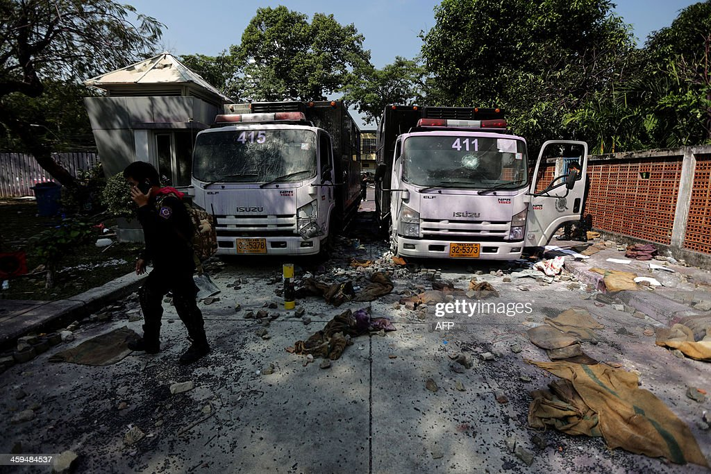 A Thai anti riot policeman (L) talks on his mobile phone in front of abandoned police trucks at a stadium in Bangkok on December 27, 2013. Thai police fired tear gas on December 26 as violent clashes broke out with opposition protesters who stormed a sports stadium in the capital to try to prevent political parties registering for elections.