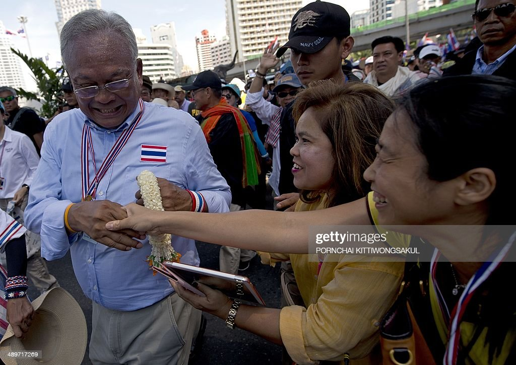Thai anti-government protest leader <a gi-track='captionPersonalityLinkClicked' href=/galleries/search?phrase=Suthep+Thaugsuban&family=editorial&specificpeople=5734971 ng-click='$event.stopPropagation()'>Suthep Thaugsuban</a> (L) shakes hands with his supporters during a rally in Bangkok on May 12, 2014. Thailand's authorities warned on May 11 that opposition efforts to hand power to an unelected regime risked unleashing new violence, as rival protesters prepared for a showdown over the fate of the crippled government.