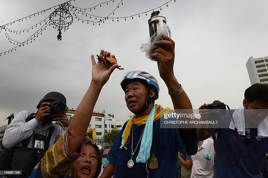 A Thai anti-government protester holds a tear-gas canister which was earlier fired by police during a protest in Bangkok on November 24, 2012. Thai police fired tear gas and detained dozens of people as tensions flared at an anti-government protest on November 24 in Bangkok, the scene of several outbreaks of violent unrest in recent years. AFP PHOTO/Christophe ARCHAMBAULT