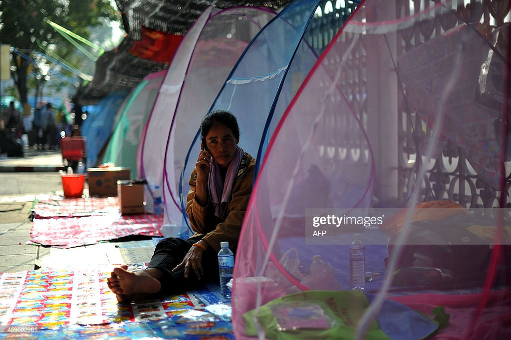 A Thai anti-government protester talks on her mobile phone at a protest site outside the Government House in Bangkok on December 28, 2013. A Thai anti-government protester was killed and several others wounded after an unknown gunman opened fire on December 28, at a rally site near the government headquarters in Bangkok, emergency services said.