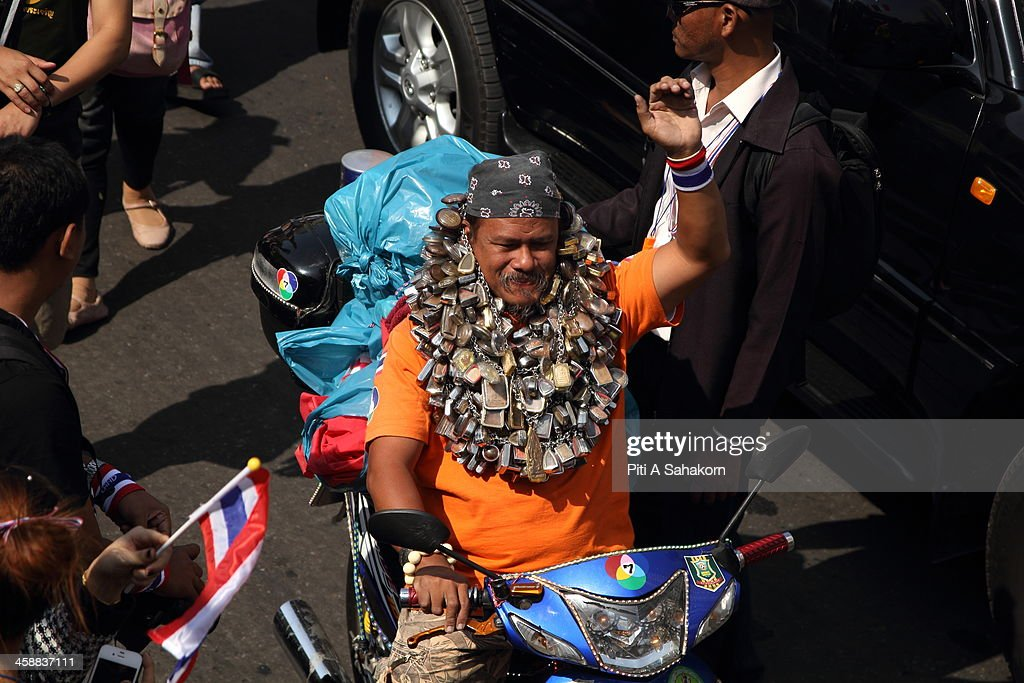 A Thai anti-government protester wears a huge Buddha amulet necklace during a rally on Taksin road in Bangkok. More than one million anti-government protesters massed ahead of a major rally aimed at toppling the Prime Minister, paralysing parts of central Bangkok. The Election Commission (EC) has expressed concern over the mass anti-government rallies beginning today, fearing they could prevent the first day of election candidate registration on Monday. The Democrat Party said it would boycott February's general election, deepening a political crisis as protesters called for another major rally to step up efforts to oust the government and force political reforms.