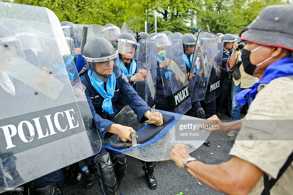 Thai anti-government protesters battle riot police during a large anti government protest on November 24, 2012 in Bangkok, Thailand. The Siam Pitak group, which sponsored the protest, cited alleged government corruption and anti-monarchist elements within the ruling party as grounds for the protest. Police used tear gas and baton charges againt protesters.