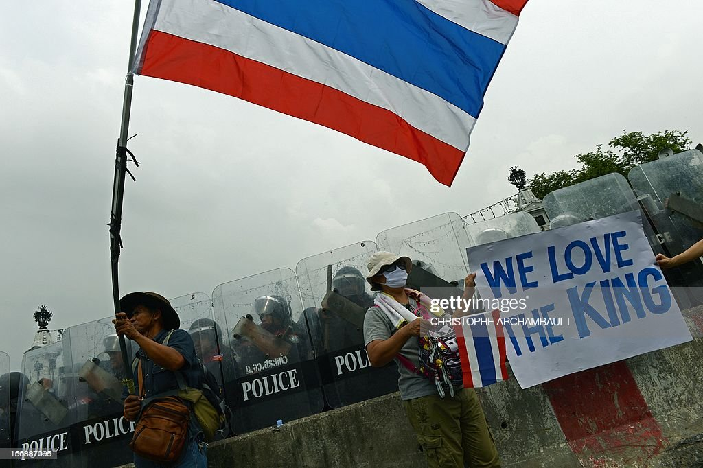 Thai anti-government protesters hold a placard as another one waves a national flag during a protest in Bangkok on November 24, 2012. Thai police fired tear gas and detained dozens of people as tensions flared at an anti-government protest on November 24 in Bangkok, the scene of several outbreaks of violent unrest in recent years. AFP PHOTO/Christophe ARCHAMBAULT