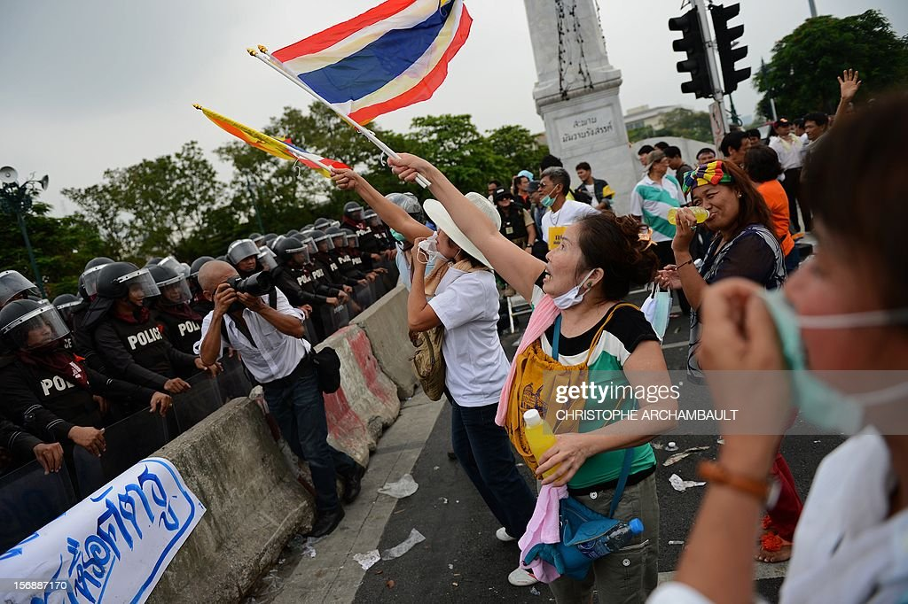 Thai anti-government protesters wave flags during a protest in Bangkok on November 24, 2012. Thai police fired tear gas and detained dozens of people as tensions flared at an anti-government protest on November 24 in Bangkok, the scene of several outbreaks of violent unrest in recent years. AFP PHOTO/Christophe ARCHAMBAULT