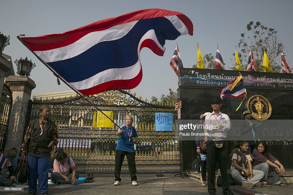 Thai anti-government protesters wave the Thai flag outside a polling station as advanced voting for the February 2nd general elections was unable to continue due to anti-government protesters blocking the polls in Bangkok January 26, 2014. An anti-government leader was shot dead and 9 others injured during election related violence today. The anti-government protesters vowed to stop all elections from taking place in the capital city. The Thai government imposed a 60-day state of emergency in Bangkok and the surrounding provinces in an attempt to cope with the on-going political turmoil but so far this decree has had no effect on the mass protests.