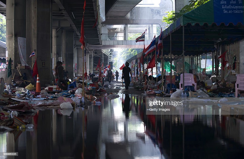 A Thai anti-government red shirt protester walks through the recently abandoned camp near the main rally site after Thai military forces dispersed the protesters on May 19, 2010 in Bangkok, Thailand. At least 5 people are reported to have died as government forces sought to overrun barricades raised in and around the city centre by anti-government protestors. Red-shirt leaders have now surrendered, ending their blockade in the aftermath of a sixth day of violence, leaving the army in control and a night time curfew to be imposed.
