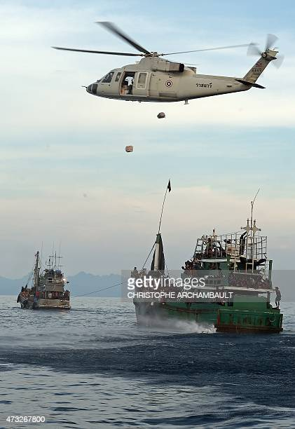 A Thai army helicopter drops food supplies near a boat carrying Rohingya migrants and drifting in Thai waters off the southern island of Koh Lipe in...