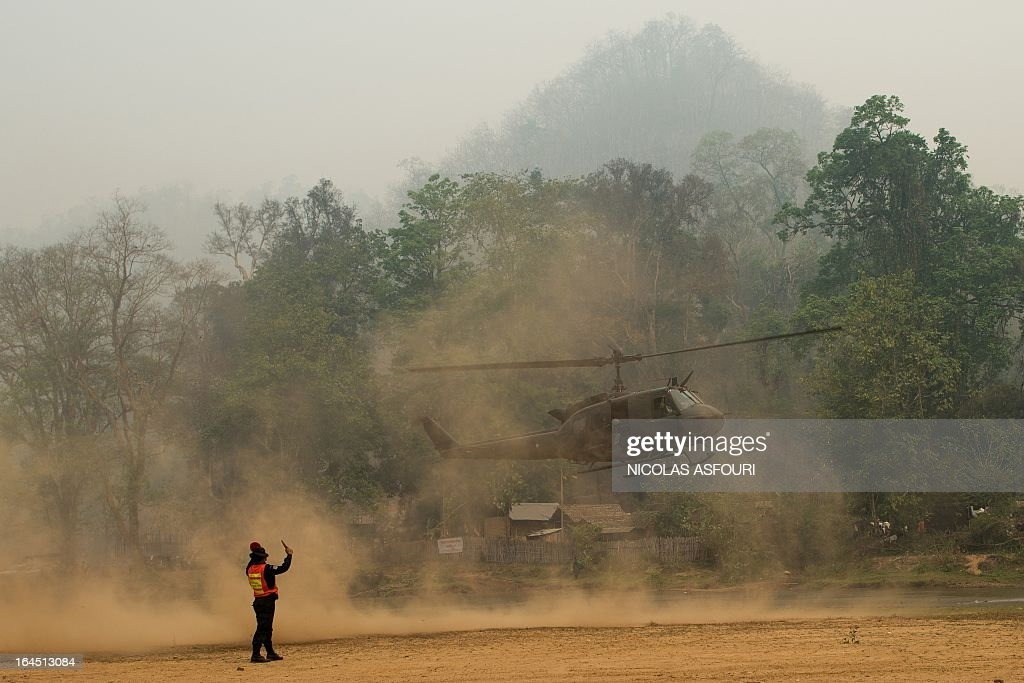 A Thai army helicopter lands at the Mae Surin camp in Mae Hong Son province on March 24, 2013. Thai rescue workers picked through the ashes of hundreds of shelters for Myanmar refugees, after a ferocious blaze swept through a camp in northern Thailand killing 35 people. Around 100 people were injured in Friday's fire at the Mae Surin camp in Mae Hong Son province, provincial governor Narumol Paravat told AFP by telephone, giving a reduced toll from the 45 dead previously stated. AFP PHOTO/ Nicolas ASFOURI