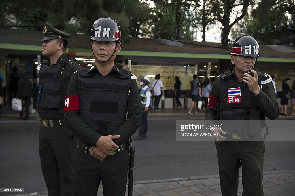 Thai army police officers secure an area at Victory monument on June 5, 2014 in Bangkok. Thailand's junta said that it was scrapping a curfew in three major beach resorts to woo back tourists in the wake of last month's military coup. AFP PHOTO/ Nicolas ASFOURI