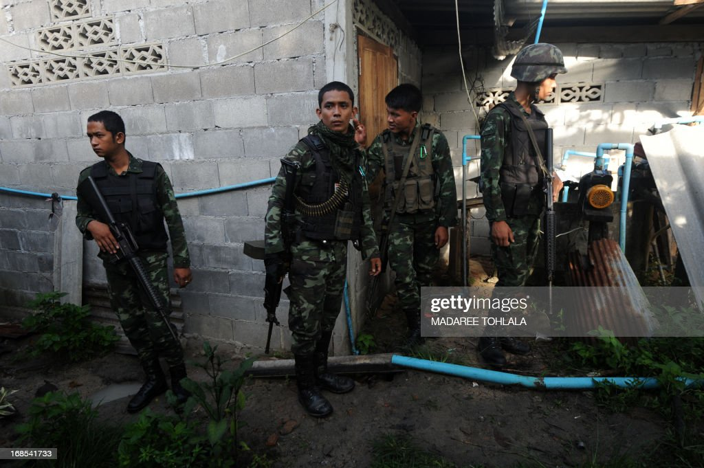 Thai army soldiers stand by as Thai police officers (not seen) inspect the body (not seen) of a suspected separatist militant who was shot dead during a clash with Thai army rangers in the Rueso district of Thailand's restive southern province of Narathiwat on May 11, 2013. More than 5,500 people have been killed in Thailand's Muslim-majority south since 2004, with shadowy insurgent groups blamed for near-daily bombings and shootings. AFP PHOTO/ Madaree Tohlala