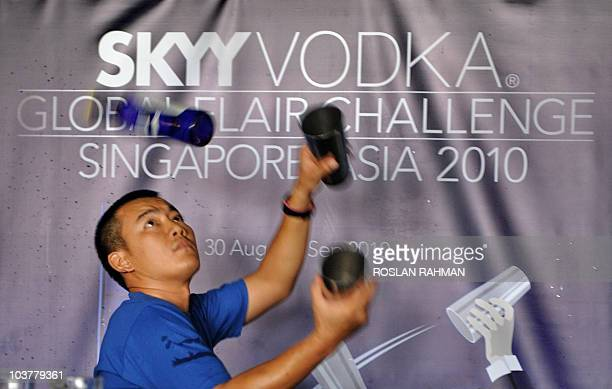 Thai bartender Songwot Chittiwuttipong exhibits his skill by juggling bottles of vodka during a regional flair bartending competition at the Skyy...