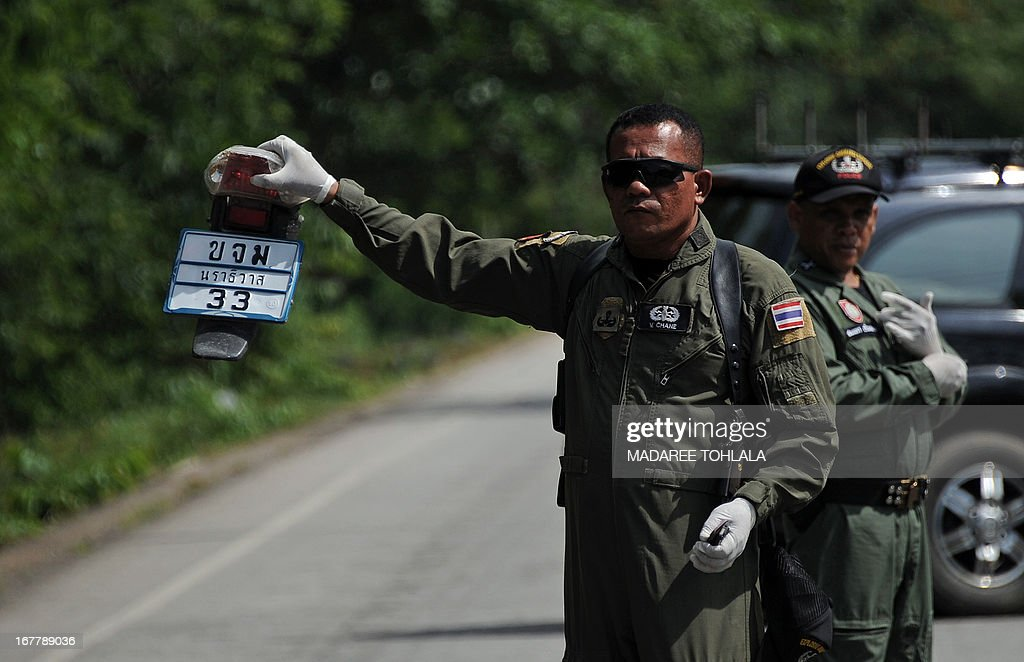 A Thai bomb squad member holds a part of a motorcycle following a roadside motorcycle bomb blast targeting a patroling police pick-up truck triggered by suspected separatist militants in the Ra-ngea district of Thailand's restive southern province of Narathiwat on April 30, 2013. More than 5,500 people have been killed in Thailand's Muslim-majority south since 2004, with shadowy insurgent groups blamed for near-daily bombings and shootings. AFP PHOTO/Madaree TOHLALA