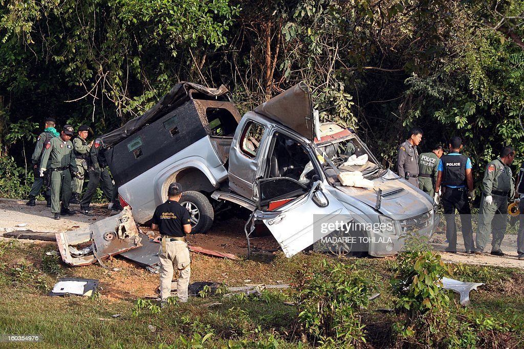 Thai bomb squad members inspect the site of a roadside bomb attack by suspected separatist militants on a pick-up car carrying soldiers in Thailand's restive southern province of Narathiwat on January 30, 2013. One soldier was killed and two injured in the attack. More than 5,300 people, both Buddhist and Muslim, have been killed since 2004, according to local conflict monitor Deep South Watch. AFP PHOTO/Madaree TOHLALA